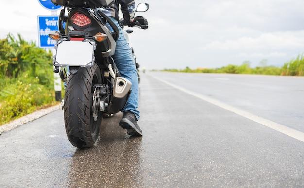 Zbliżenie motocykl motorower jeździ przez kałużę na mokrej drodze w deszczu