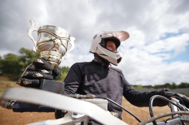 Zbliżenie: motocyklista odnoszący sukcesy w kasku, zdobywając mistrzostwo motocykla, jeżdżąc na motocyklu i trzymając kubek