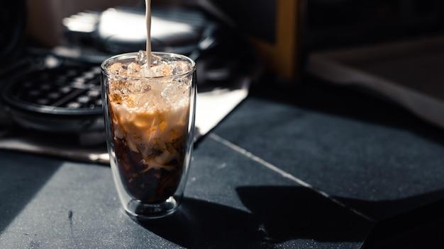 Zbliżenie mrożonej kawy podawanej na czarnym stole w kawiarni