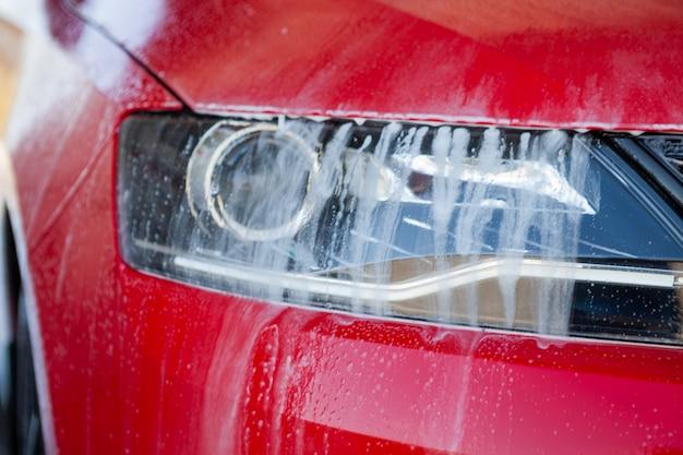 Zbliżenie myjnia samochodowa. mycie nowoczesnego samochodu mydłem pod wysokim ciśnieniem