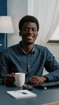 Zbliżenie na afroamerykańskiego czarnoskórego freelancera uśmiechającego się do kamery