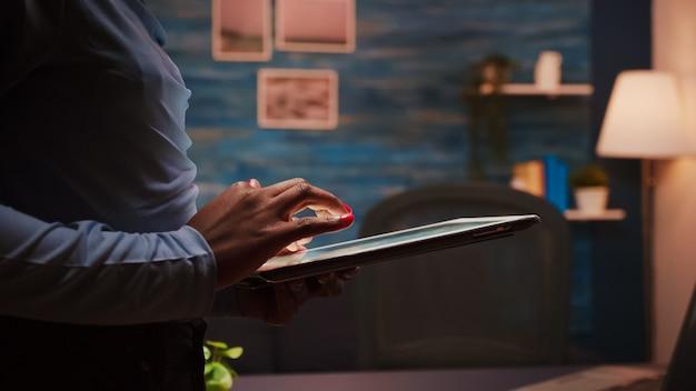 Zbliżenie na afrykańskiego pracownika wysyłającego sms-y, wysyłającego i czytającego wiadomości podczas jej przerwy stojącej w salonie późno w nocy. skupiony czarny pracownik korzystający z nowoczesnej technologii sieci bezprzewodowej przepracowany