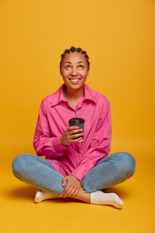 Zbliżenie na atrakcyjną beztroską młodą kobietę siedzącą na podłodze