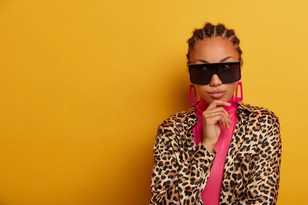Zbliżenie na atrakcyjną beztroską młodą kobietę w okularach przeciwsłonecznych