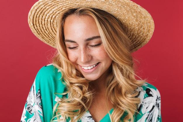 Zbliżenie na atrakcyjną młodą blondynkę ubraną w letnią sukienkę i słomkowy kapelusz stojącą na białym tle nad różową ścianą, śmiejąca się