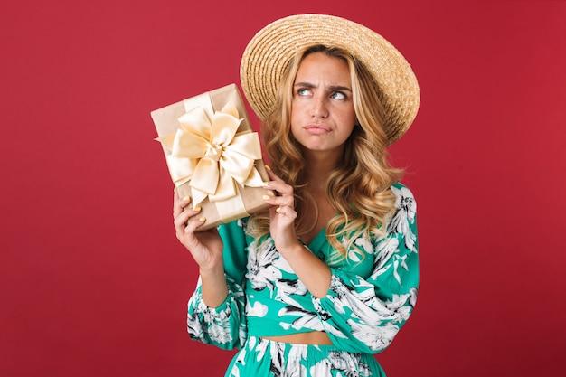 Zbliżenie na atrakcyjną, zdezorientowaną młodą blondynkę ubraną w letnią sukienkę i słomkowy kapelusz, stojącą na białym tle nad różową ścianą, pokazującą pudełko na prezent