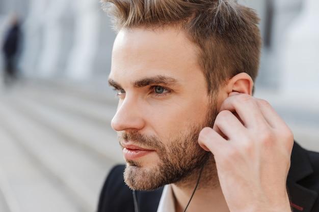 Zbliżenie na atrakcyjnego młodego biznesmena noszącego słuchawki na murach miasta