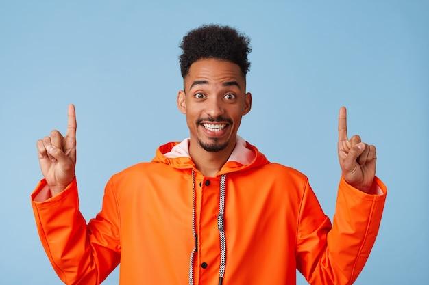 Zbliżenie na bardzo szczęśliwy młody atrakcyjny afroamerykanin ciemnoskóry facet nosi pomarańczowy płaszcz przeciwdeszczowy, uśmiecha się szeroko i wskazuje palcami w górę na miejsce.