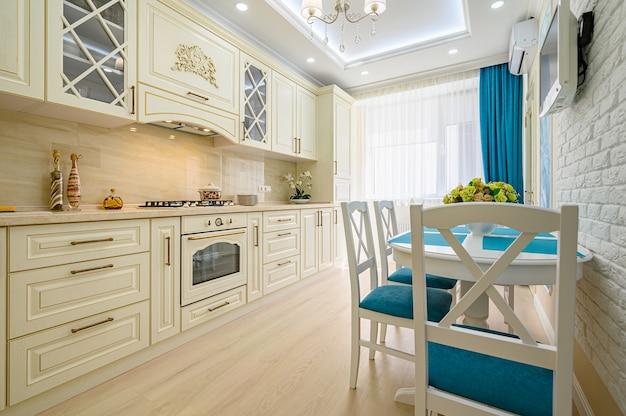 Zbliżenie na beżową, białą i cyjanową współczesną klasyczną kuchnię wewnętrzną zaprojektowaną w stylu prowansalskim, wszystkie meble z otwartymi drzwiami i szufladami