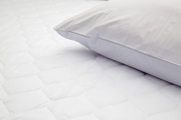 Zbliżenie na białą poduszkę na łóżku w sypialni