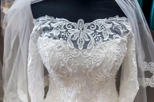 Zbliżenie na białej sukni ślubnej na manekinie