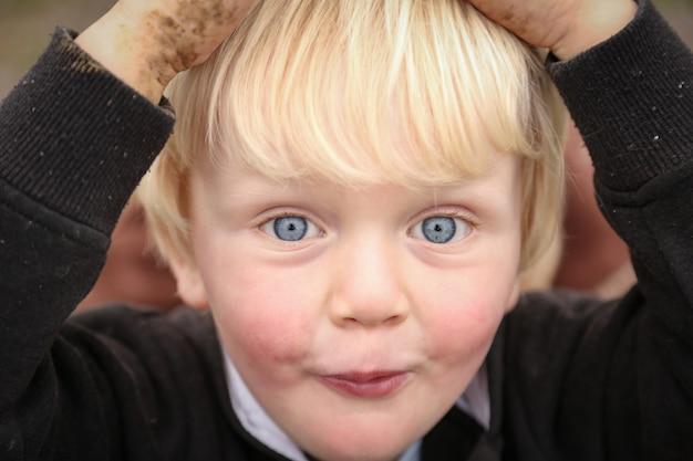 Zbliżenie na biały kaukaski dzieciak z niebieskimi oczami, trzymający jego głowę zabłoconymi rękami