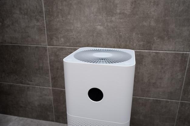 Zbliżenie na biały oczyszczacz powietrza w pomieszczeniach. środek do czyszczenia kurzu i alergii w domu.