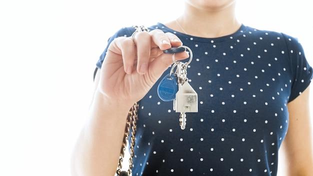 Zbliżenie na białym tle widok kobiety trzymającej klucze z nowego domu.