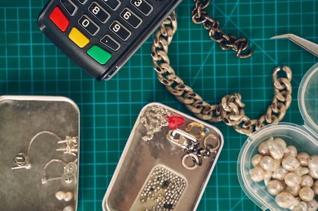 Zbliżenie na biurko z perłami i metalowym naszyjnikiem oraz białymi koralikami w miejscu pracy