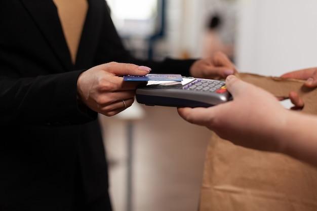 Zbliżenie na biznes kobieta trzyma kartę kredytową z pos