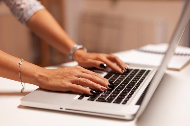 Zbliżenie na bizneswoman pracy na komputerze w terminie późno w nocy