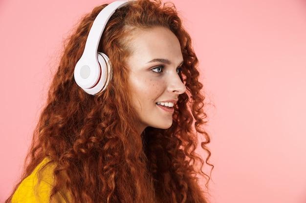 Zbliżenie na boczny portret atrakcyjnej uśmiechniętej młodej kobiety z długimi kręconymi rudymi włosami stojącej na białym tle, słuchającej muzyki przez słuchawki