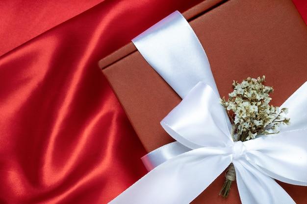 Zbliżenie na boże narodzenie lub nowy rok czerwone pudełko z białą wstążką i suszonymi kwiatami