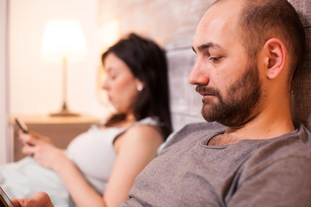 Zbliżenie na brodatego męża za pomocą smartfona przed snem. żona w tle.