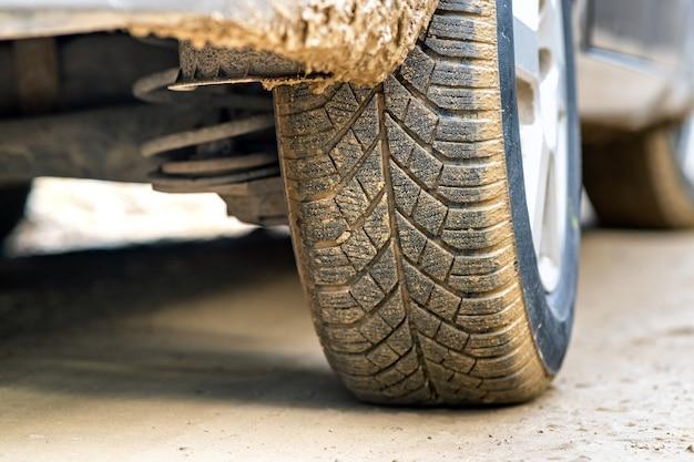 Zbliżenie na brudne koło samochodu z gumową oponą pokryte żółtym błotem.