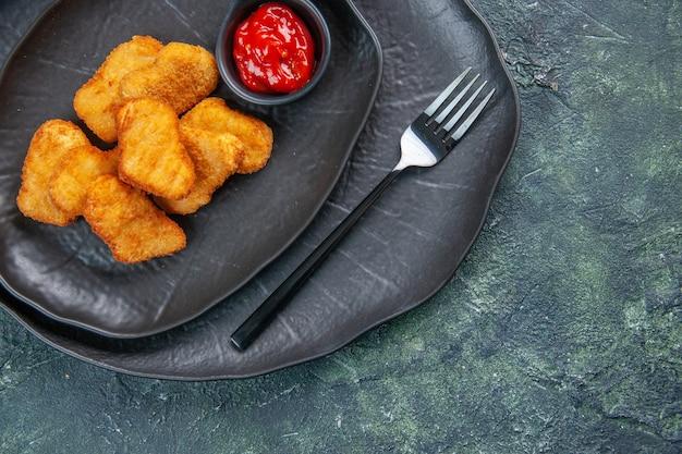 Zbliżenie na bryłki kurczaka i widelec do ketchupu w czarnych talerzach na ciemnej powierzchni
