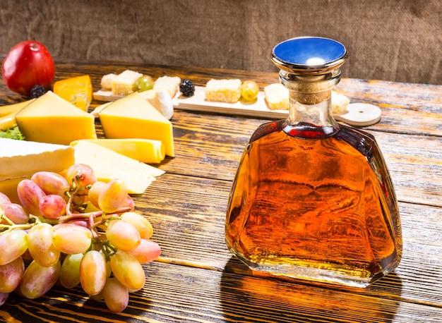 Zbliżenie na butelkę alkoholu na rustykalnym drewnianym stole z klinami sera i winogron w ciepłym otoczeniu