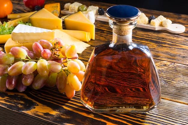 Zbliżenie na butelkę alkoholu na rustykalnym drewnianym stole z różnymi serami i winogronami z jasnym oświetleniem bocznym