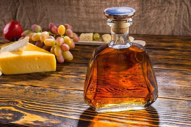 Zbliżenie na butelkę alkoholu na rustykalnym drewnianym stole z serem i winogronami i miejsce na kopię