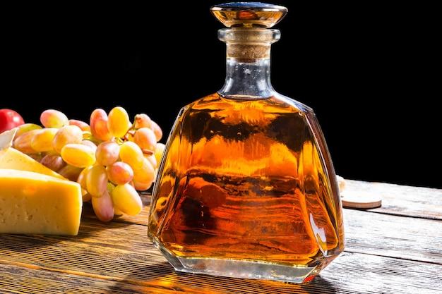 Zbliżenie na butelkę alkoholu na rustykalnym drewnianym stole z serem i winogronami z jasnym podświetleniem i czarnym tłem
