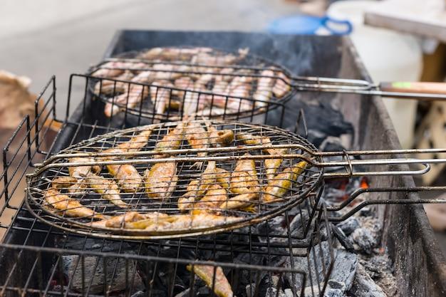 Zbliżenie na całą rybę gotującą się na gorącym węglu drzewnym podczas palenia grilla na świeżym powietrzu