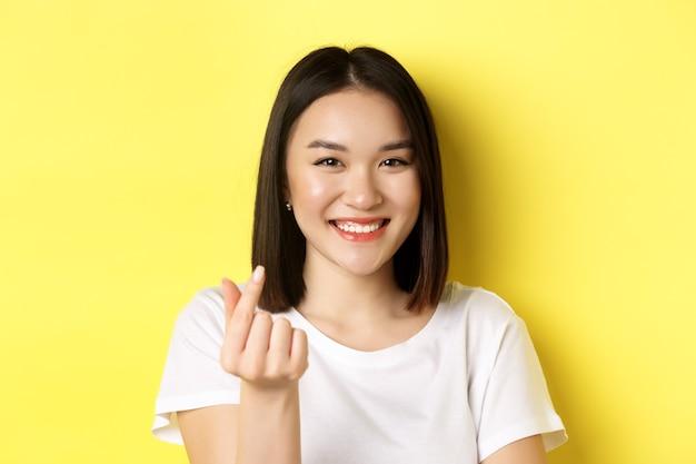 Zbliżenie na całkiem azjatycką dziewczynę w białej koszulce, uśmiechając się i pokazując palec serce, stojąc na żółtym.