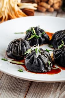 Zbliżenie na chińskie czarne pierogi z sosem sojowym i zieloną cebulą