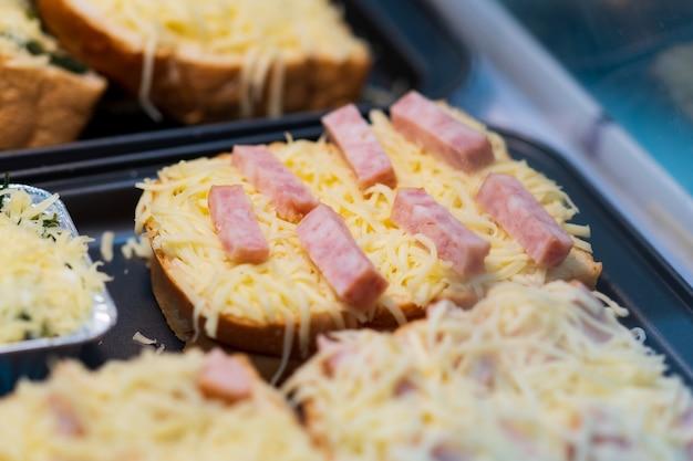 Zbliżenie na chleb szynkowy z serem, tajski targ uliczny
