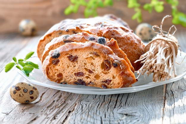 Zbliżenie na chleb wielkanocny na rustykalnym drewnie ze świeżymi liśćmi i jajkami przepiórczymi. tradycyjny niemiecki deser na święta wielkanocne