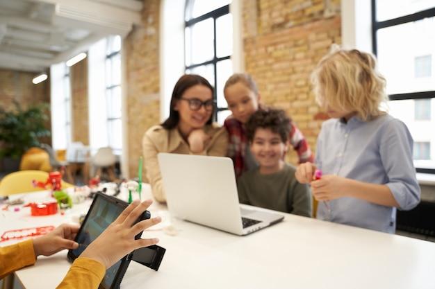 Zbliżenie na chłopca grającego w gry przy użyciu komputera typu tablet podczas nauczyciela klasy macierzystej pokazującej naukową robotykę