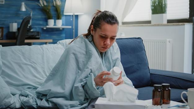Zbliżenie na chorą kobietę patrzącą na butelkę tabletek i leków