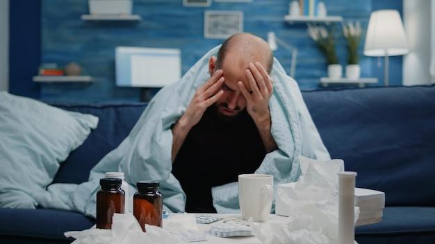 Zbliżenie na chorego dorosłego z bólem głowy pocierającym skronie