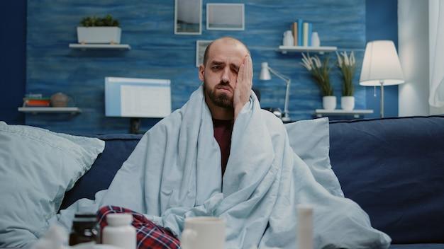 Zbliżenie na chorego mężczyznę z bólem głowy pocierającym skronie