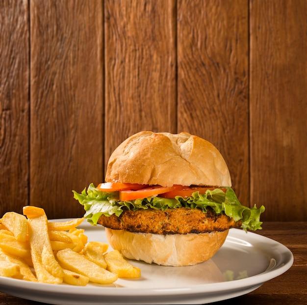 Zbliżenie na chrupiącego burgera z kurczaka z sałatą i pomidorem.