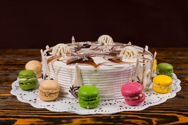 Zbliżenie na ciasto z różnymi czekoladowymi ozdobami, w pobliżu makaroników, na drewnianym biurku