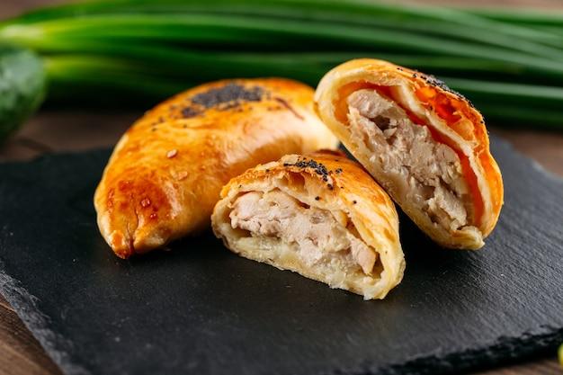 Zbliżenie na cięte orientalne danie pieczone ciasto z mięsem kurczaka samsa na czarnym kamiennym talerzu