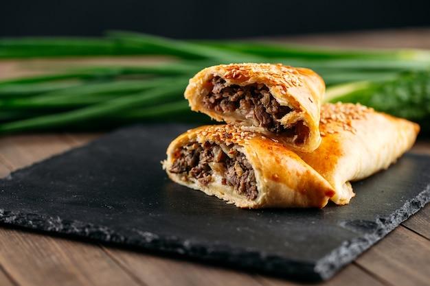Zbliżenie na cięte orientalne danie pieczone ciasto z mięsem samsa na czarnym kamiennym talerzu