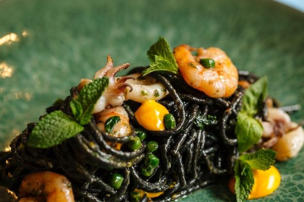 Zbliżenie na czarne spaghetti z owocami morza i sosem szafranowym