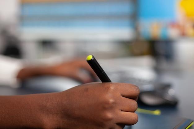 Zbliżenie na czarnego projektanta zdjęć, który edytuje obraz klienta za pomocą ołówka z rysikiem, ilustrator rysujący na tablecie graficznym