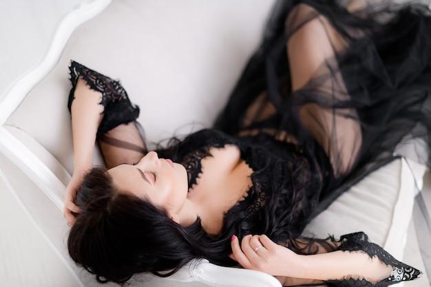 Zbliżenie na czarującą brunetkę w czarnym peniuarze leży i pozuje do kamery