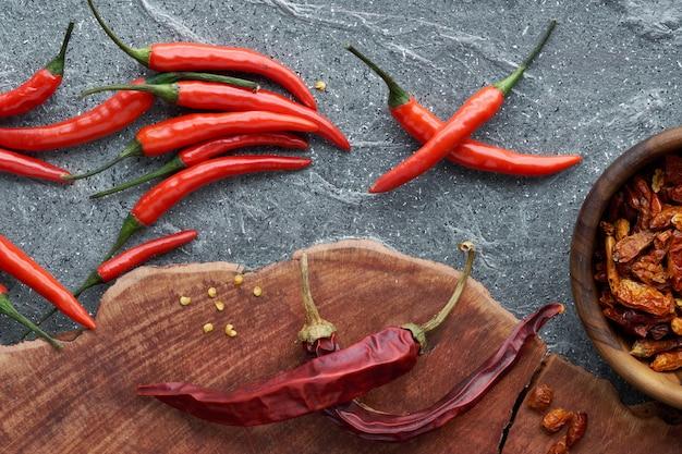 Zbliżenie na czerwone papryczki chili, świeże i suche, na drewnie i szarym kamieniu