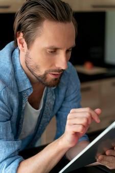 Zbliżenie na człowieka korzystającego z urządzenia cyfrowego w domu
