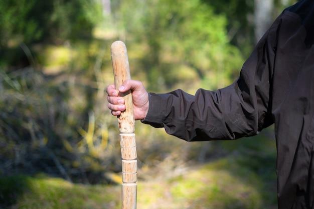 Zbliżenie na człowieka posiadającego laskę w lesie