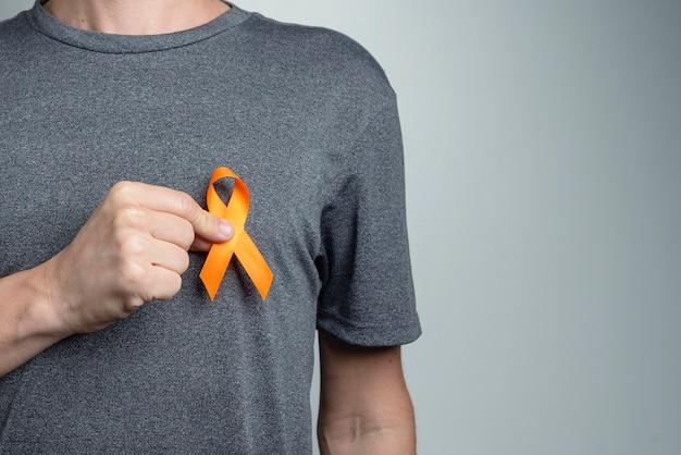 Zbliżenie na człowieka posiadającego pomarańczową wstążkę na jego koszuli